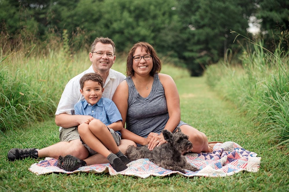 Family of 3 with dog sitting in field