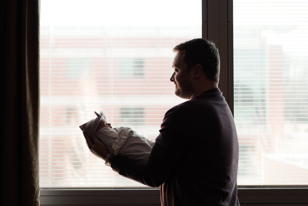 silhouette of dad with baby girl in front of window at hospital
