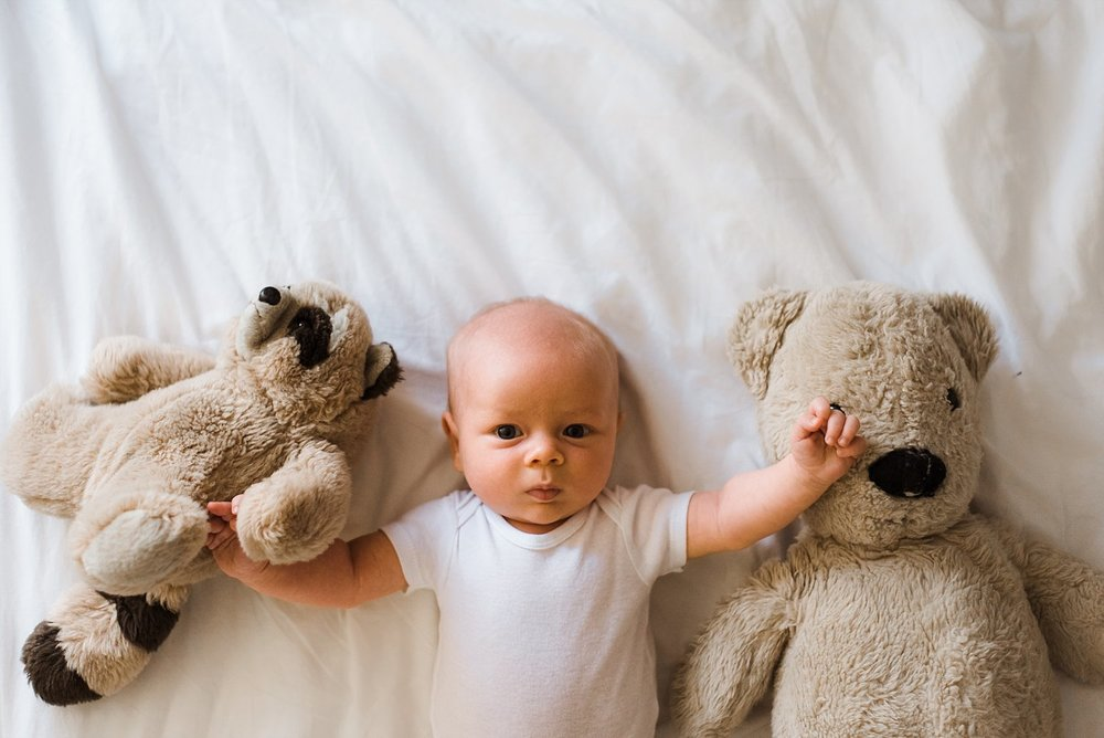 newborn baby boy with parents stuffed animals