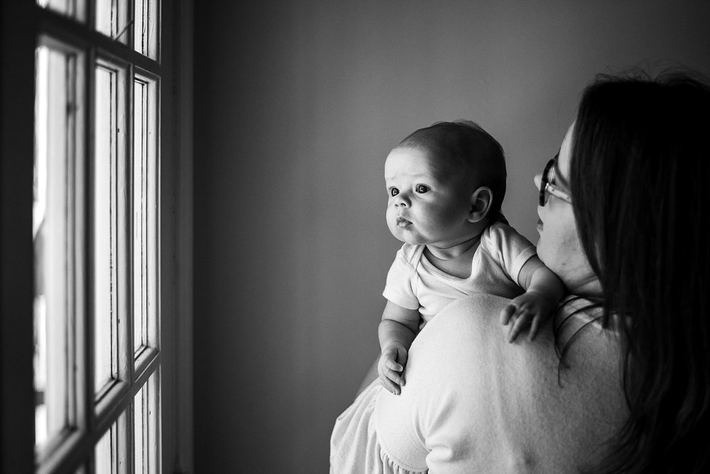baby looking at window over moms shoulder