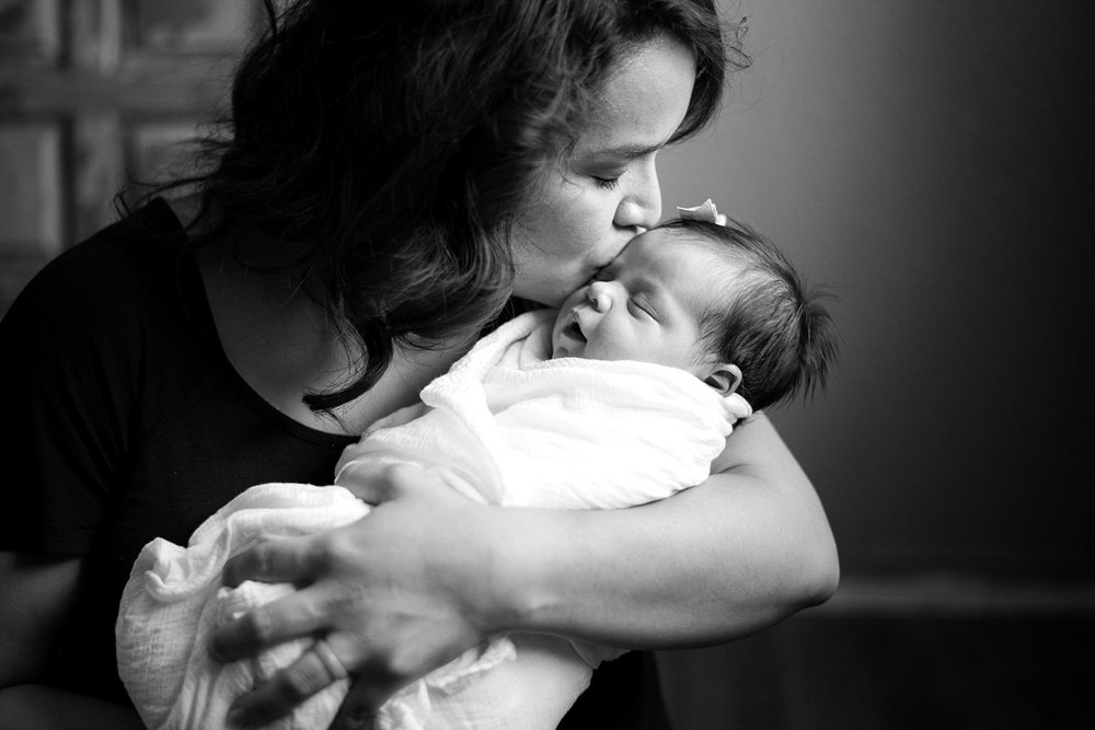 mom kissing newborn baby girl lifestyle newborn photography