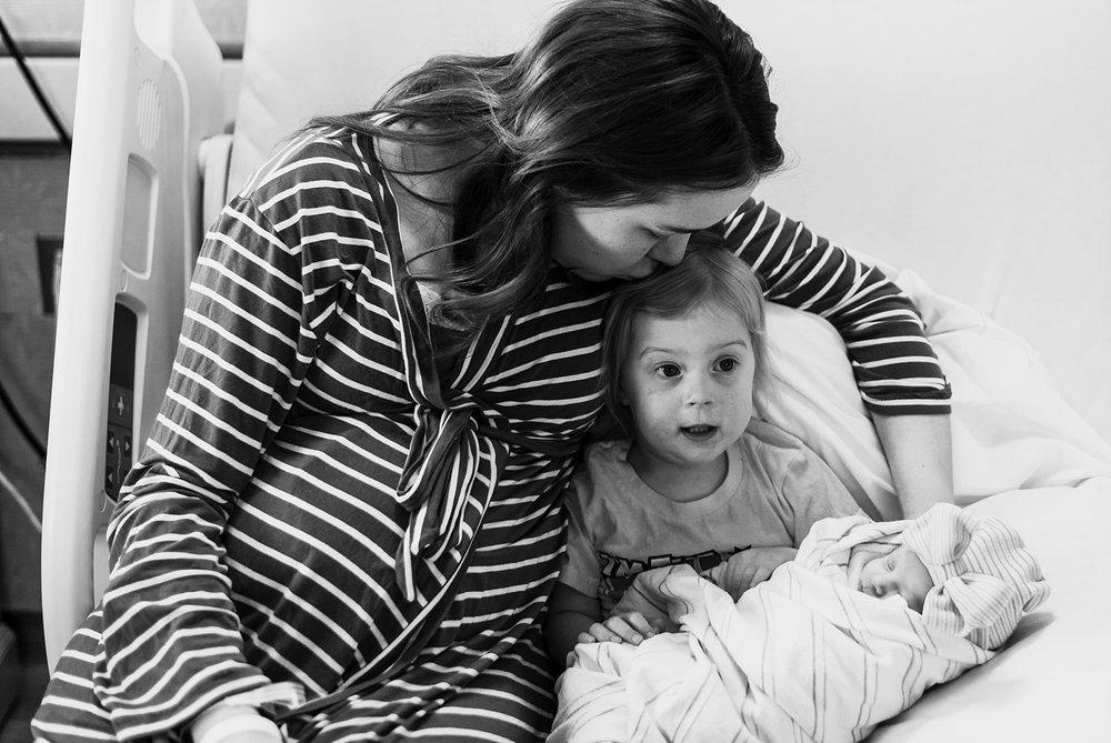 Mother kissing toddler holding newborn baby sister at Northside Atlanta Hospital