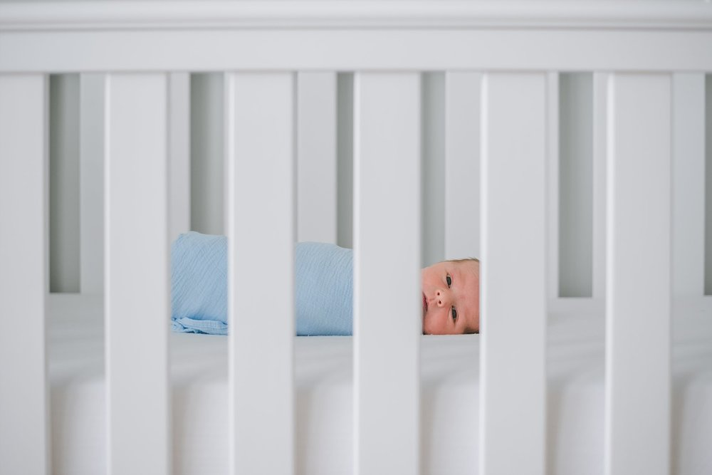 newborn baby boy swaddled looking through crib slats