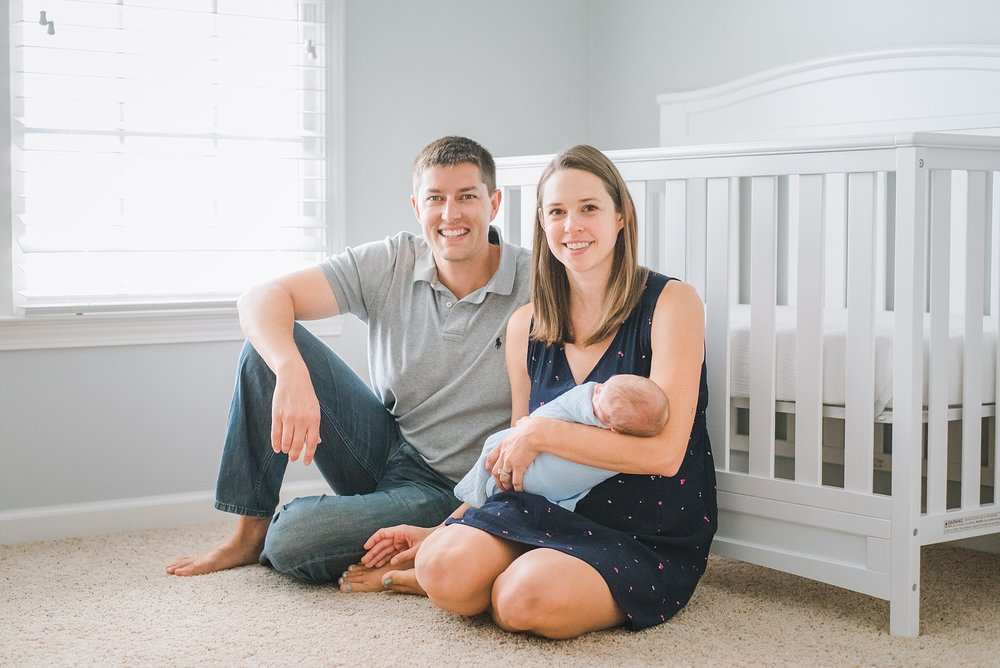 Mother and father with newborn in nursery sitting in front of crib