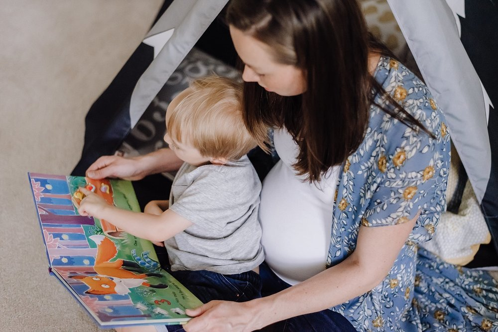 pregnant mother reading to toddler boy