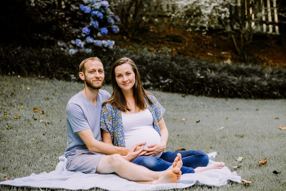 couple sitting in grass holding pregnant mother's belly