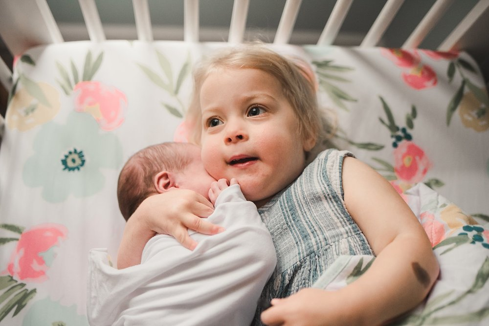 toddler hugging newborn sister