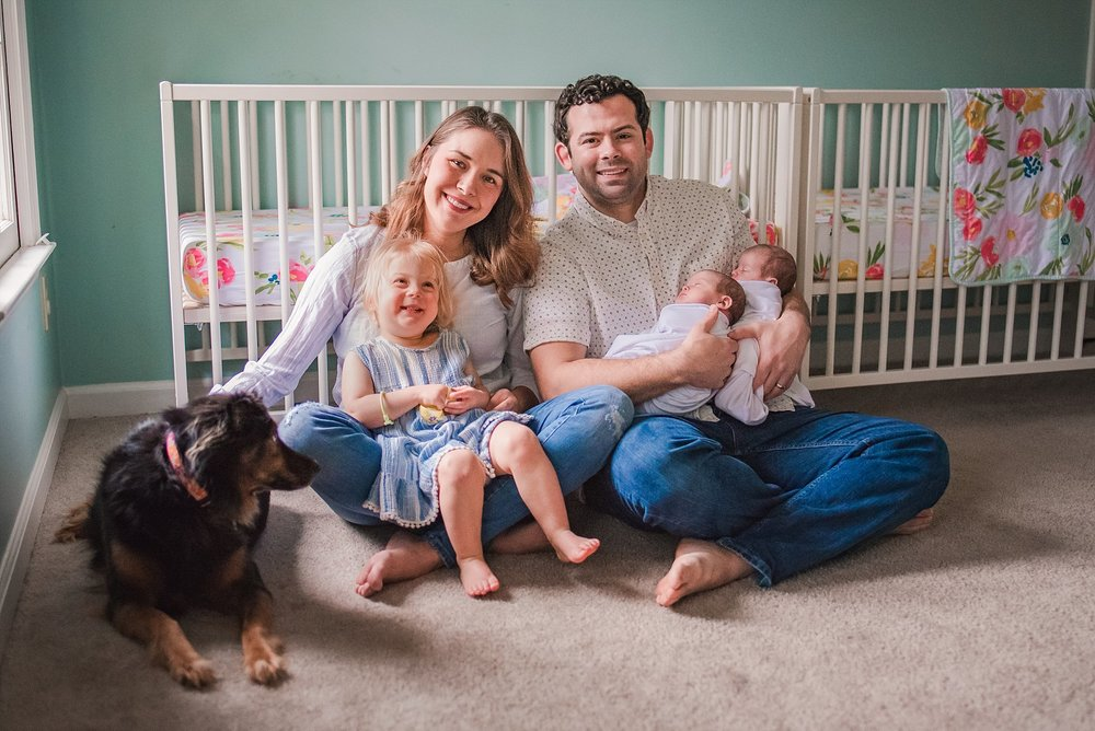 mom, dad, toddler girl, newborn twins, dog sitting in front of crib in nursery