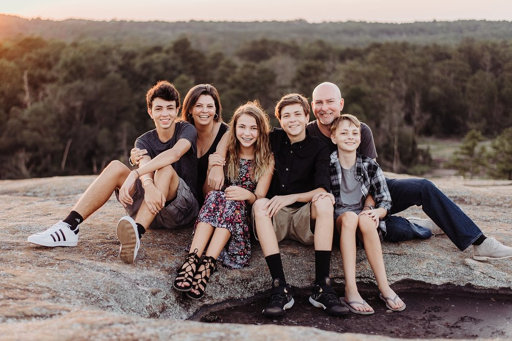 Family sitting at sunset on Arabia Mountain Atlanta