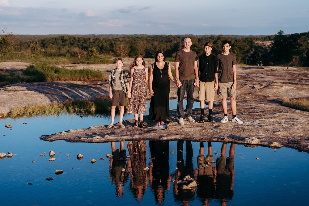 portrait of family with reflection pool at Arabia Mountain Atlanta