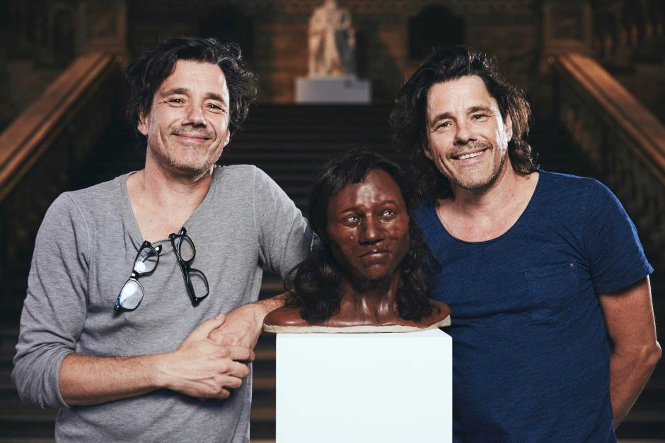Identical twin brothers Adrie and Alfons Kennis with the Cheddar Man reconstruction Image credit: © Channel 4/Plimsoll Productions