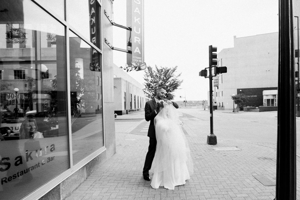 candid urban photograph of bride and groom with restaurant onlookers in Saint Paul, MN