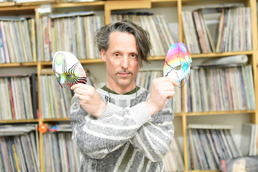 Eddie Ruscha at his studio in 2019, holding two of his original masks. Photo: Cameron Murray