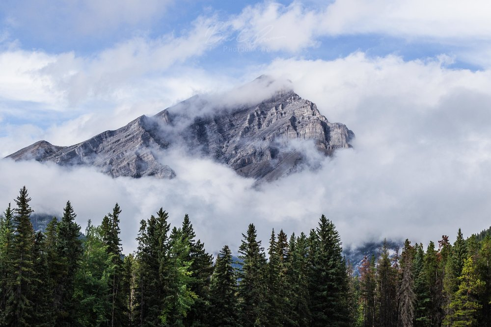 Concealed by clouds. Mountains emerging above Banff Town