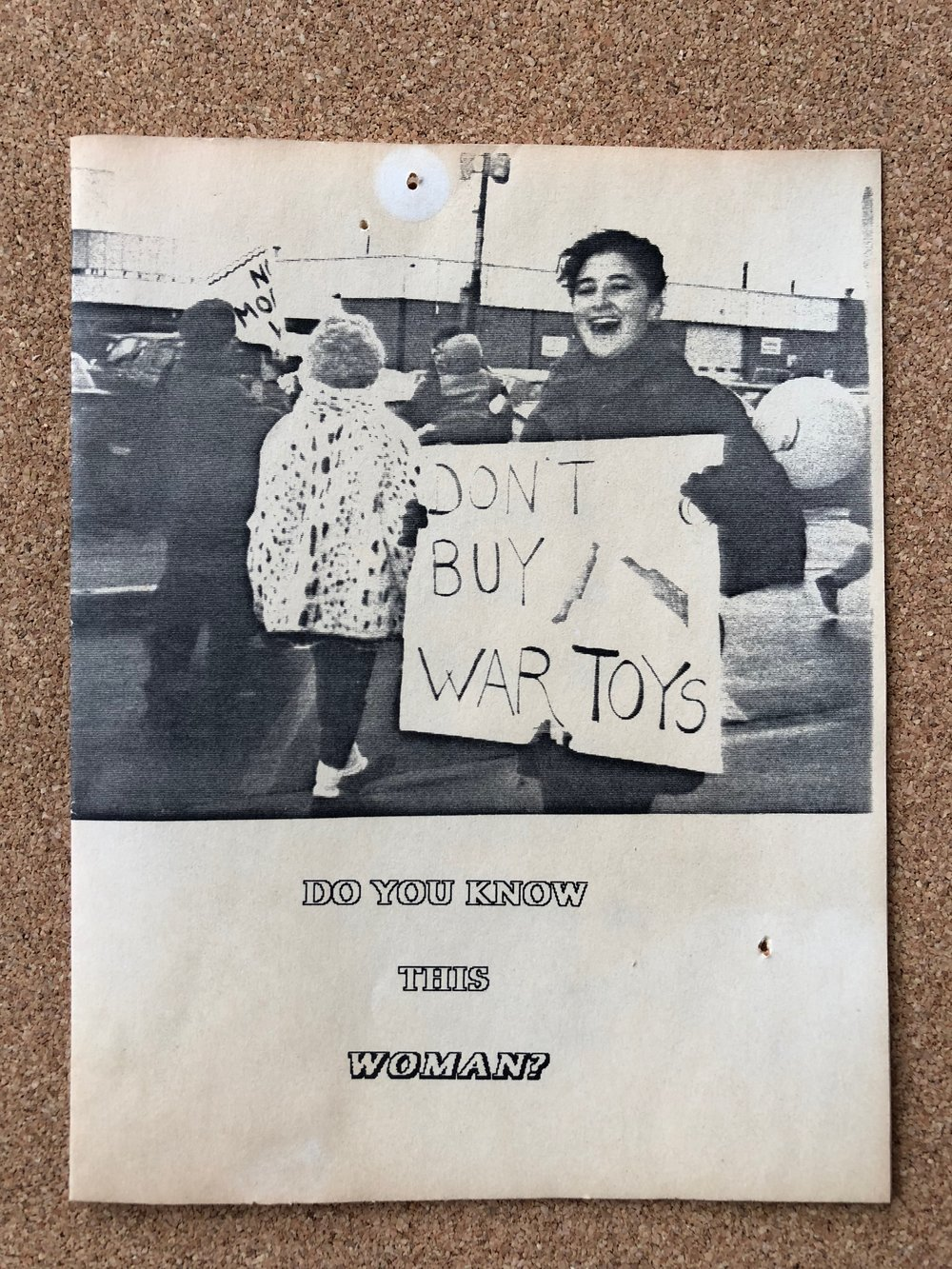 """Do You Know This Woman?"" (holding ""Don't Buy War Toys"" sign)"