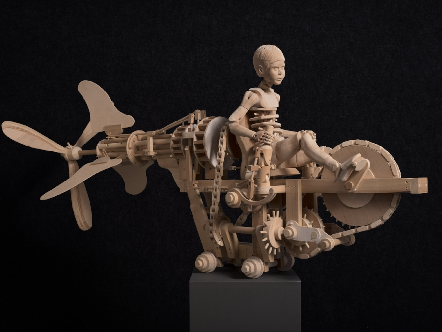 """PROPELLED BOY""  56x26x20   Fully Articulating Wooden Mechanical Carving."