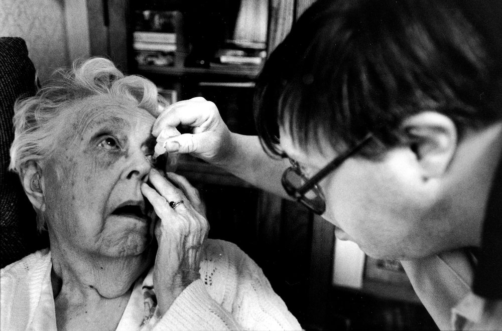 John Joyce puts eyedrops in his mother Doris' eyes before bed in their home in Bowdoinham, Maine.
