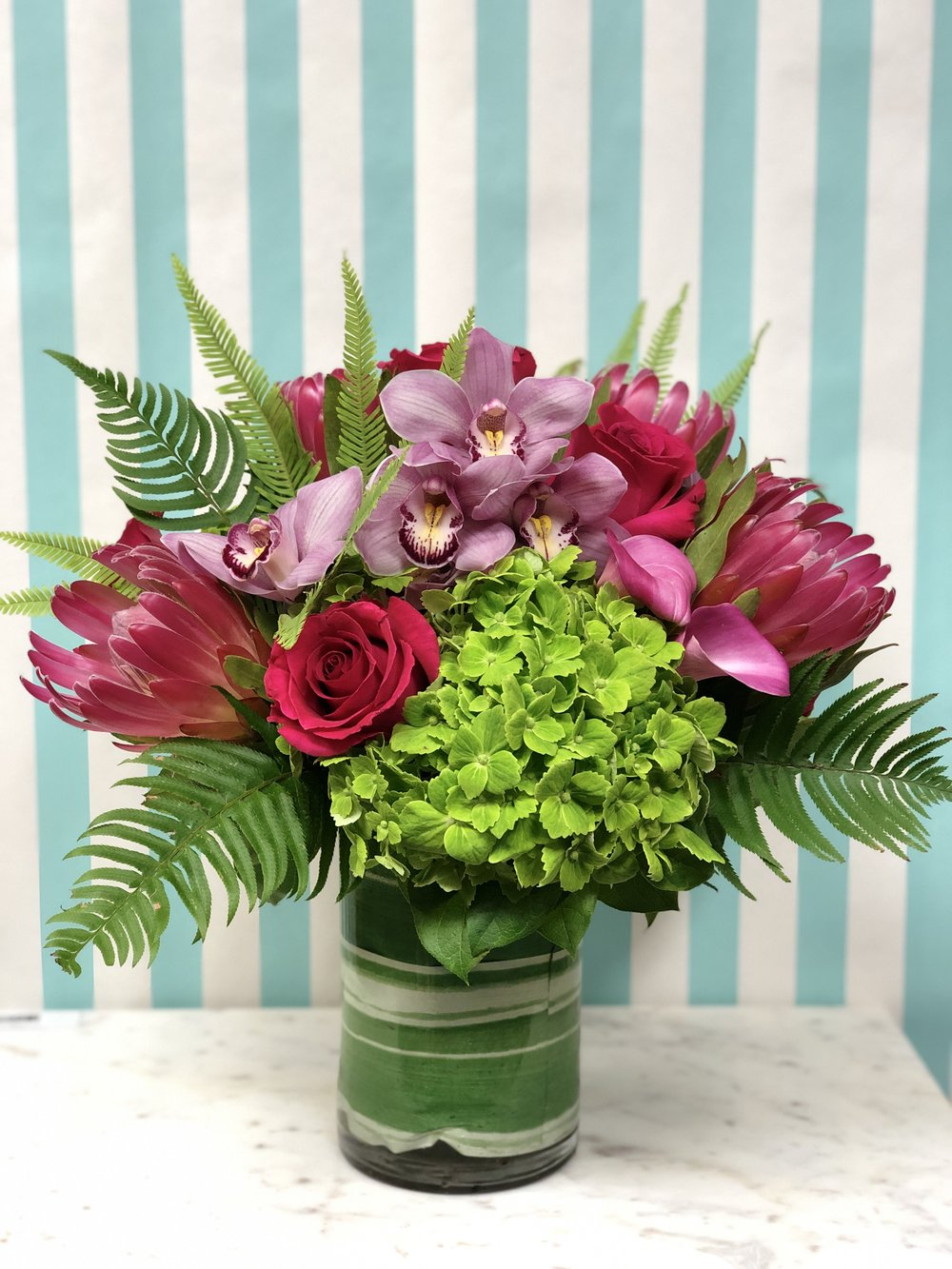 Jungle Love- $225   This modern selection of tropical flowers will be sure to please the most discerning Valentine. Protea, cymbidium, mini callas, hydrangea, rose, and fern in an 8x6 vase.