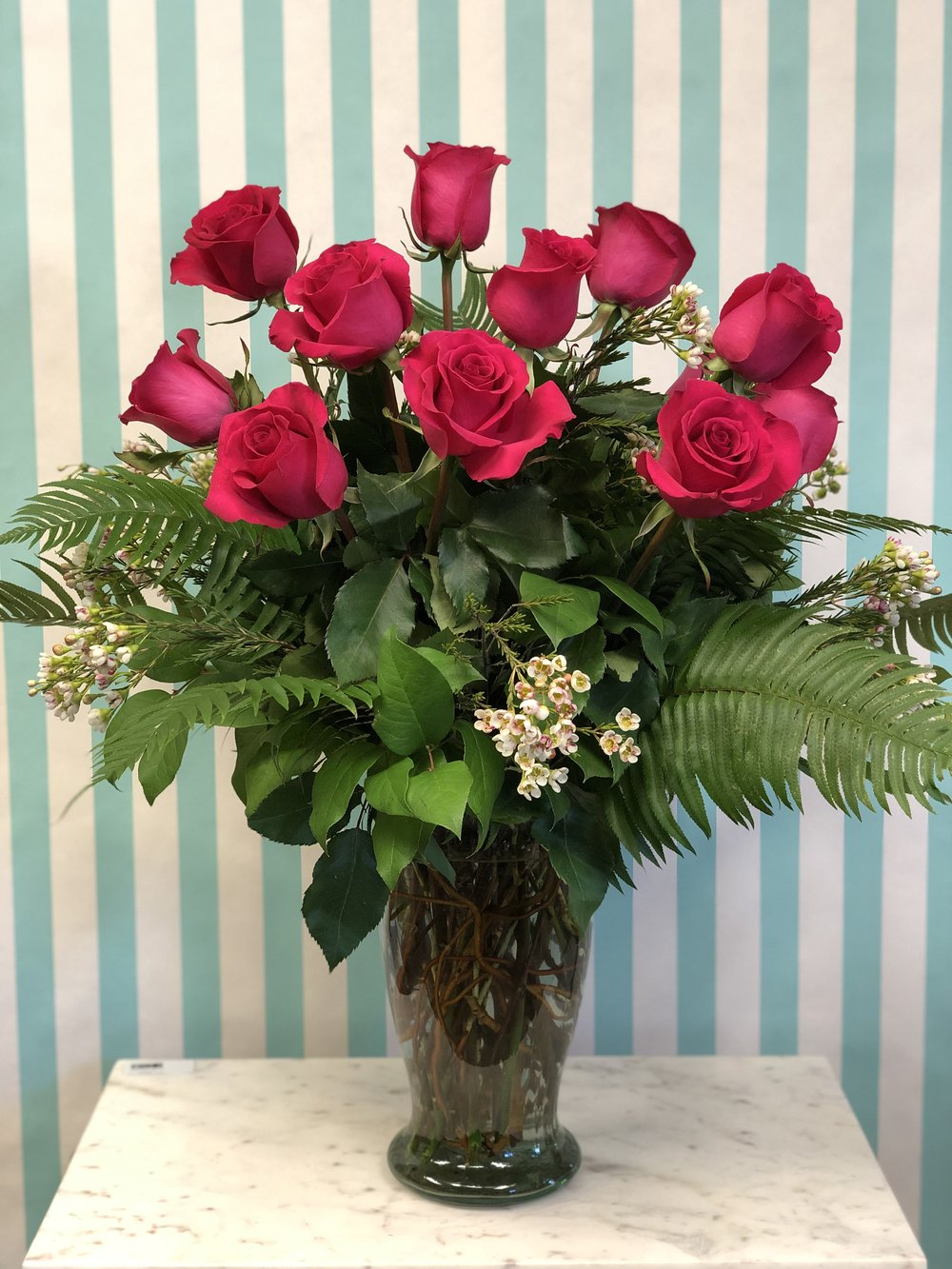 1 Dozen Roses in Vase- $120   Roses, wax flower, flat fern, and lemon leaf in a 14in vase. Colors may vary unless specified.