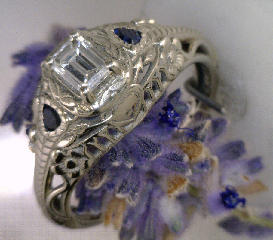 Antique ring with Emerald cut diamond and 2 trillion cut sapphire.png