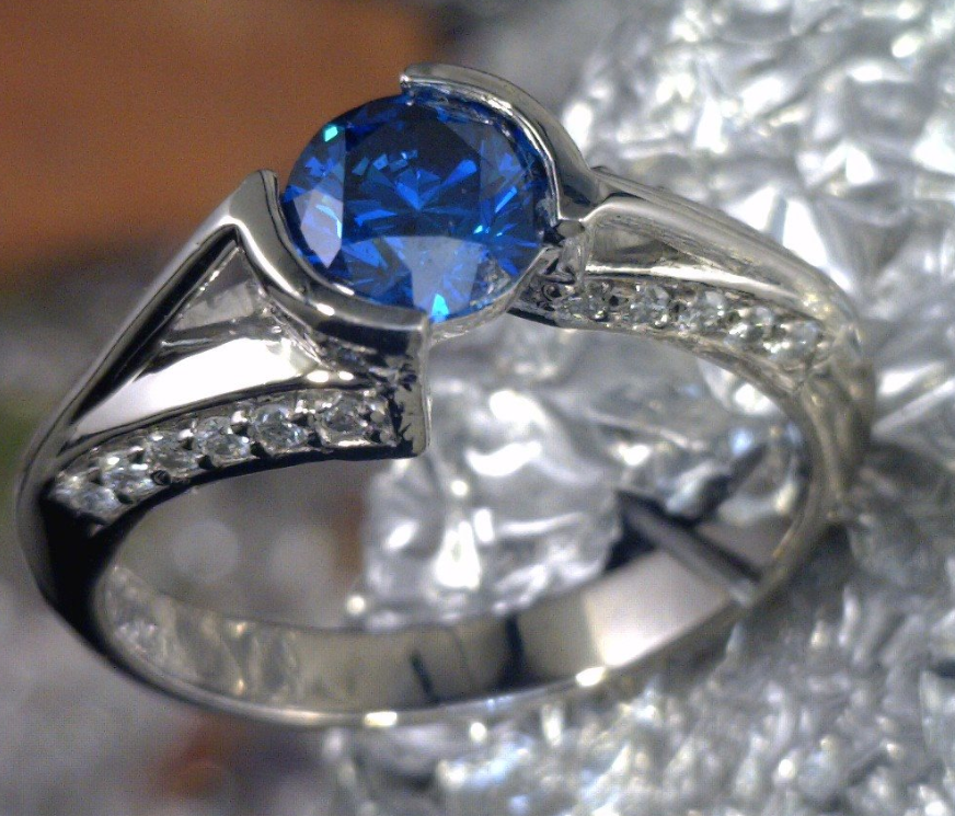 Blue diamond with white diamond side stones cast in Palladium.png
