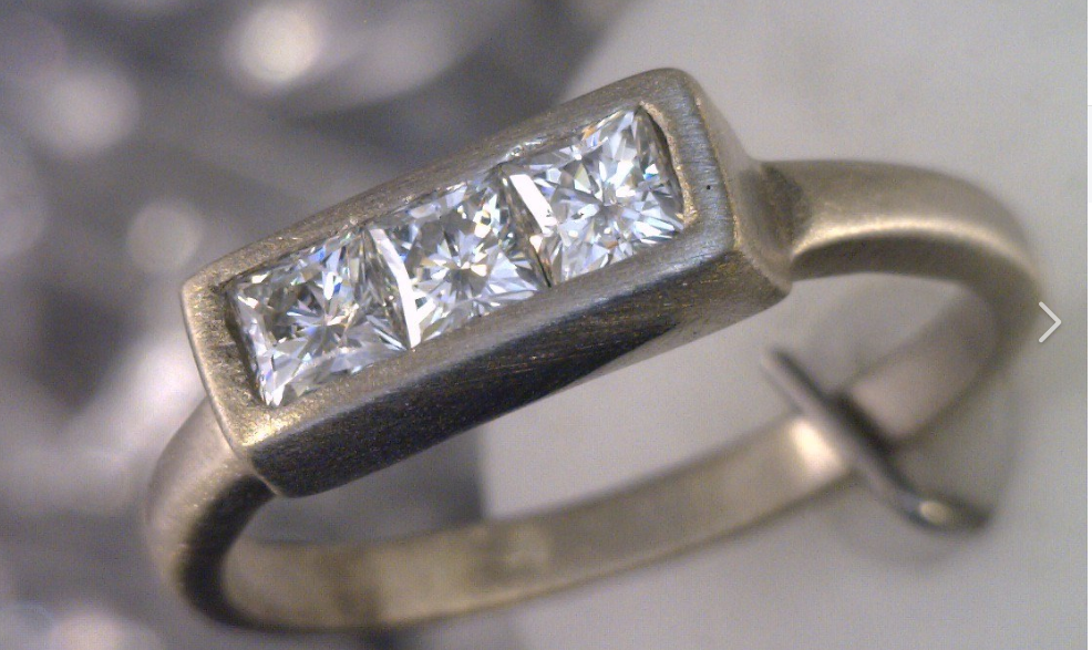 Brushed palladium ring with three princess cut diamonds.png