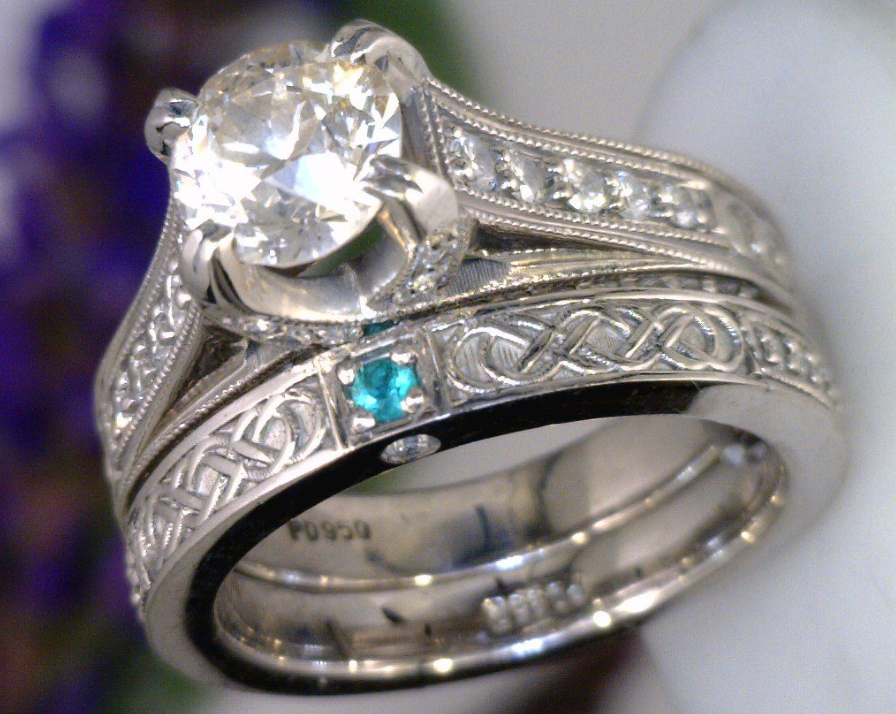 Celtic inspired wedding set with a 1 carat center diamond and a green Emerald accent stone.png