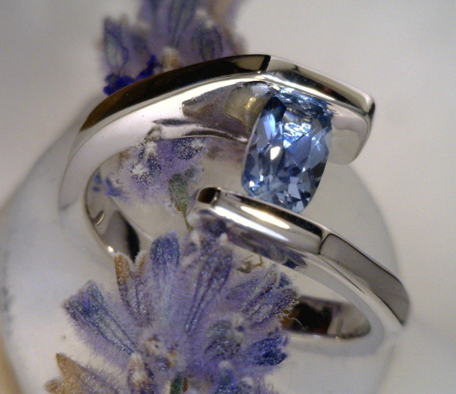 Cusion cut Montana sapphire in a palladium bypass ring.png