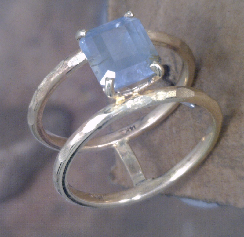 Emerald cut light blue Montana Sapphire on hammered yellow gold double bands.png