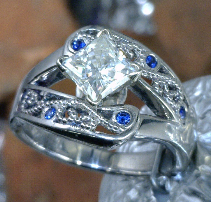 Fillagree ring with princess cut center diamond and Sapphire accent stones.png