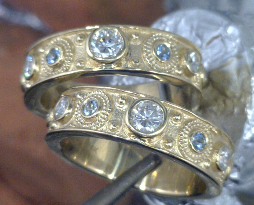 Matching yellow gold diamond rings with Aquamarine side stones.png