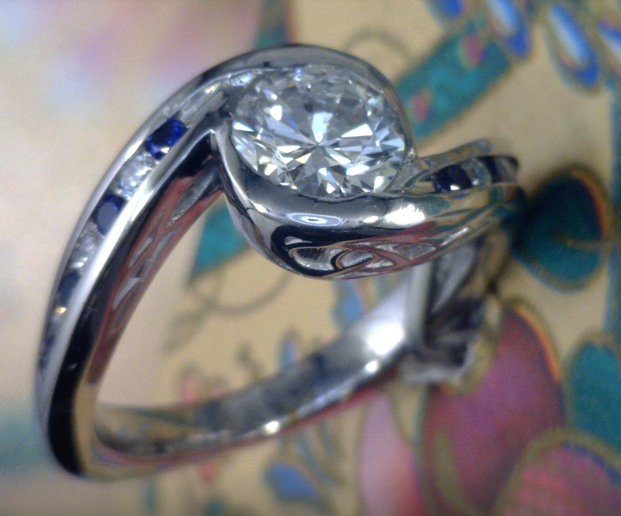 One carat diamond with diamond and sapphire side stones with celtic knot cast in Palladium.png