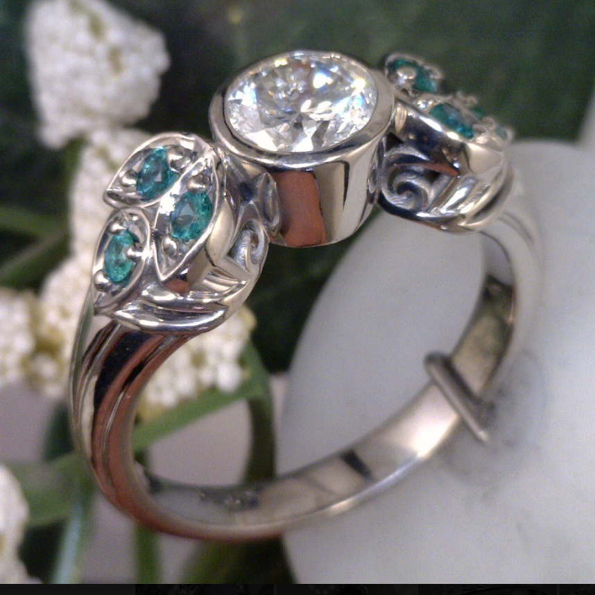 Palladium ring with 1 carat diamond center and emerald side stones.png