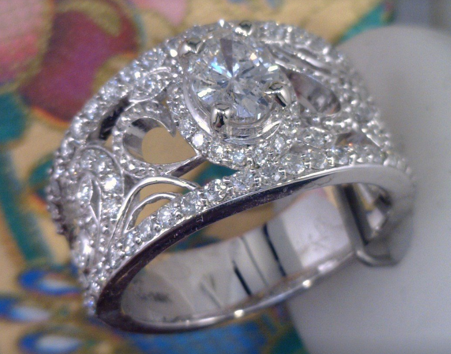 Wide band filagree cluster diamond ring with oval center diamond.png