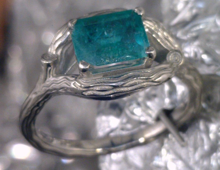 Wood grain inspired setting with emerald cut emerald stone.png