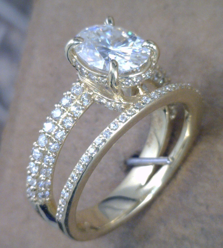 Yellow gold with diamond cluster sides and Oval diamond center stone.png