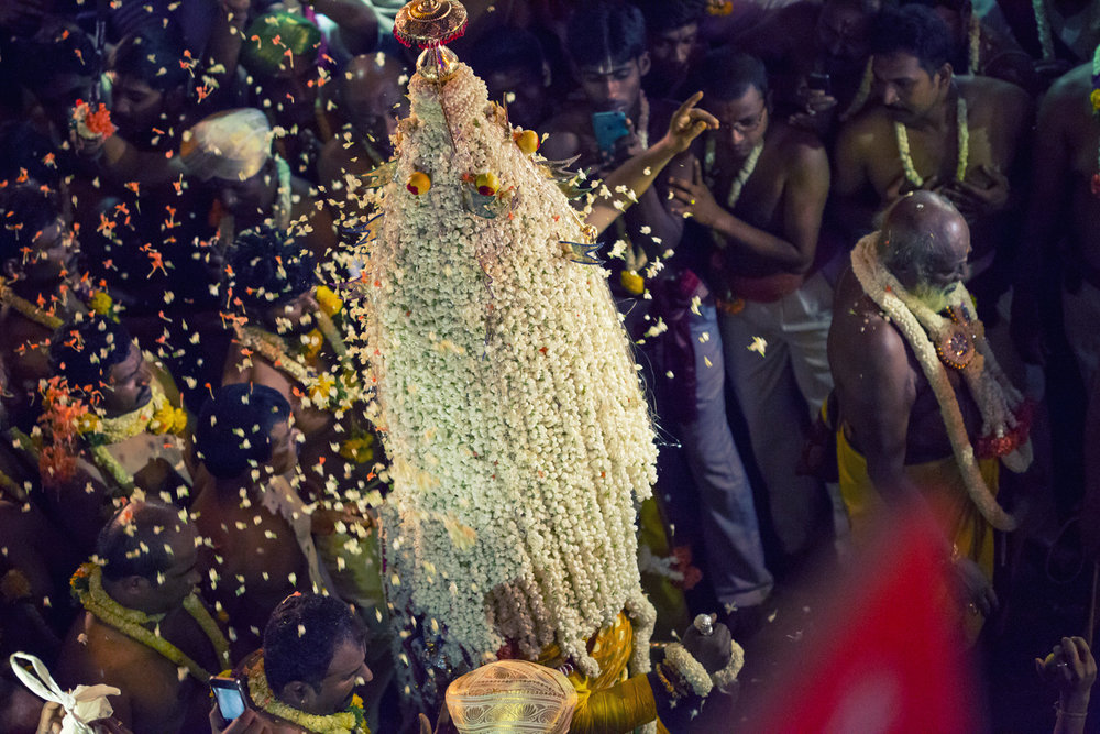 Devotees throw heaps of jasmine at the Karaga as it makes its rounds in the Pete.
