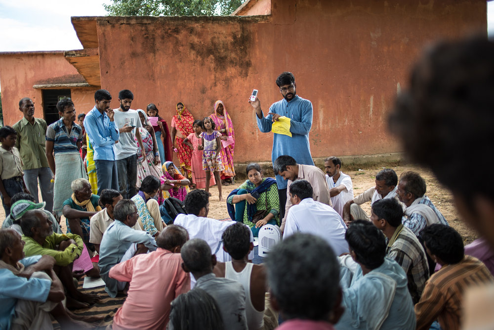Vivek Goyal, a Greenpeace campaigner   (below)   explaining   'Radio Sangarsh'   to the people of Suhira. It was launched to enable people to directly communicate with a larger audience by recording their opinions and grievances through a cell phone, which in turn would be put up on a website.