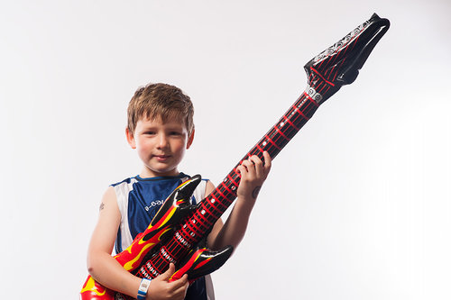 A child plays an air guitar © Robert Lowdon