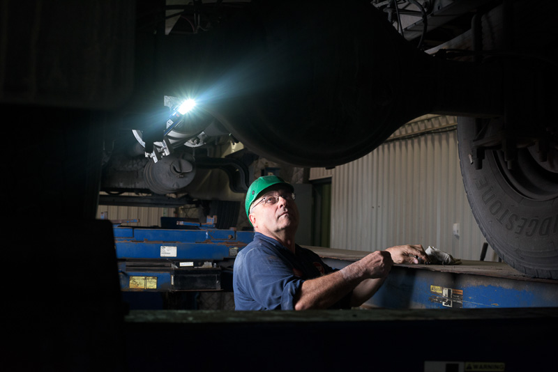 A mechanic works on a large postal truck on an industrial hoist. In this image I light the subject from the left of the frame to give the effect of the trouble lighting the scene.
