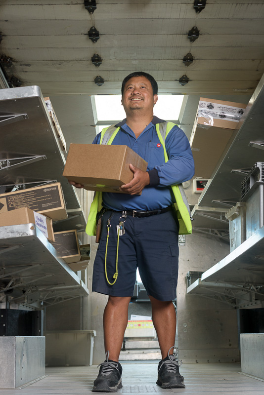 A worker loads the back of a mail truck with parcels. Front lighting with natural lighting in back.