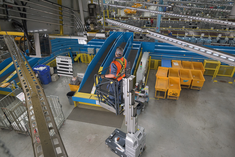 A maintenance worker inspects a conveyor belt motor. I wanted to show the sheer size of the mail plant in comparison to the worker in this image.