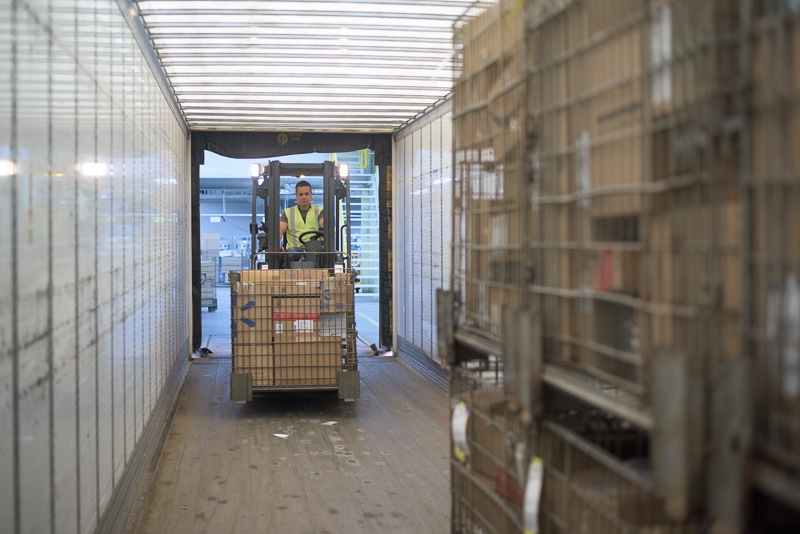 A forklift loads a truck containing parcels. This was shot with only available light.