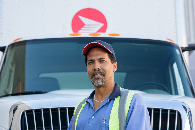 A truck driver in front of Canada Post vehicle. Placing the driver directly in front of the truck gave a meaningful image.