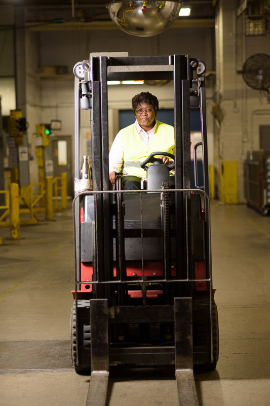 A employee drives a forklift across a dock. I used lighting placed to the left of the subject to highlight her in the environment.