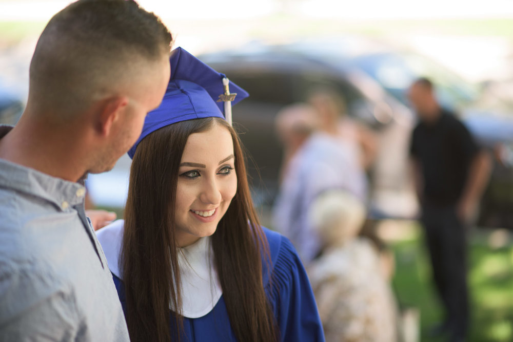 A medium close-up shot of a CDI student with a guest on graduation day. In this candid photograph, the smiling graduand greets guests prior to the ceremony. A shallow depth of field is used so that the student and guest are sharply in focus but the rest of the scene is blurred.