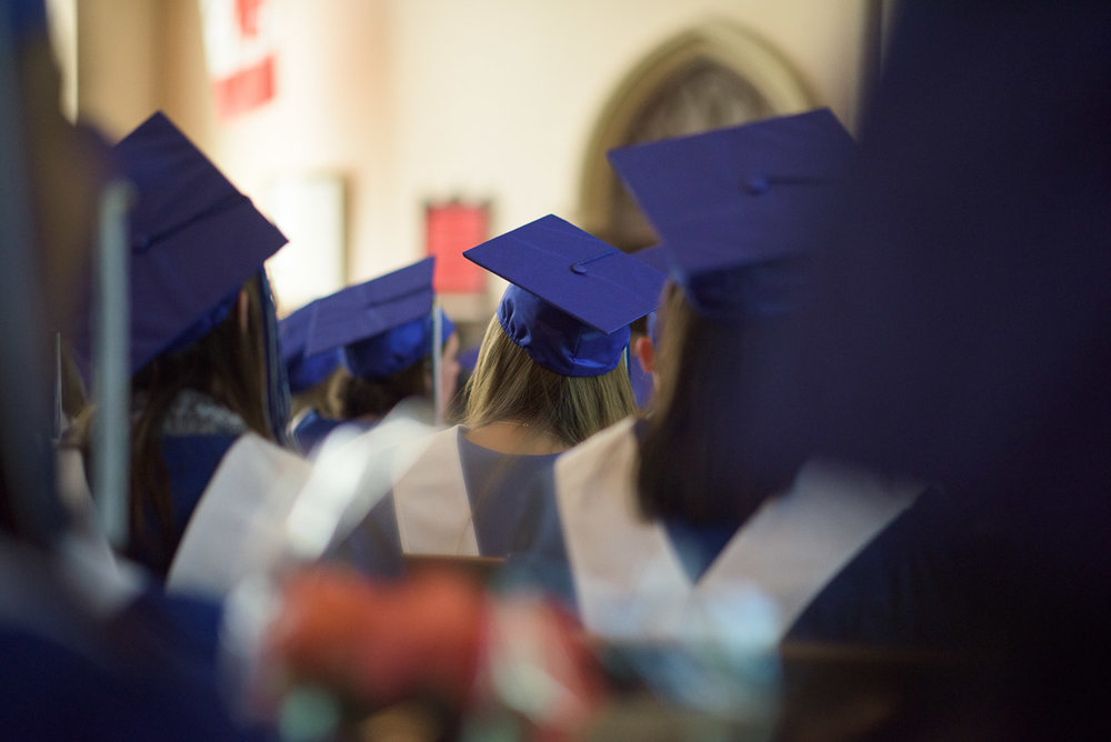 Students donning caps and gowns, sit waiting for their names to be called during the graduation ceremony. The photograph is captured at eye-level through rows of seated students, offering an interesting perspective and creating a sense of being immersed in the crowd.