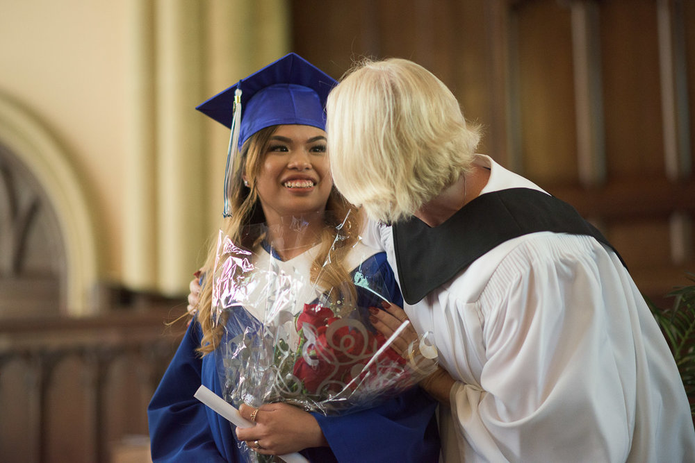 A smiling student is congratulated by her instructor. Both are dressed in academic regalia. A shallow depth of field is used to draw the eye to the student's smiling face in this celebratory moment.