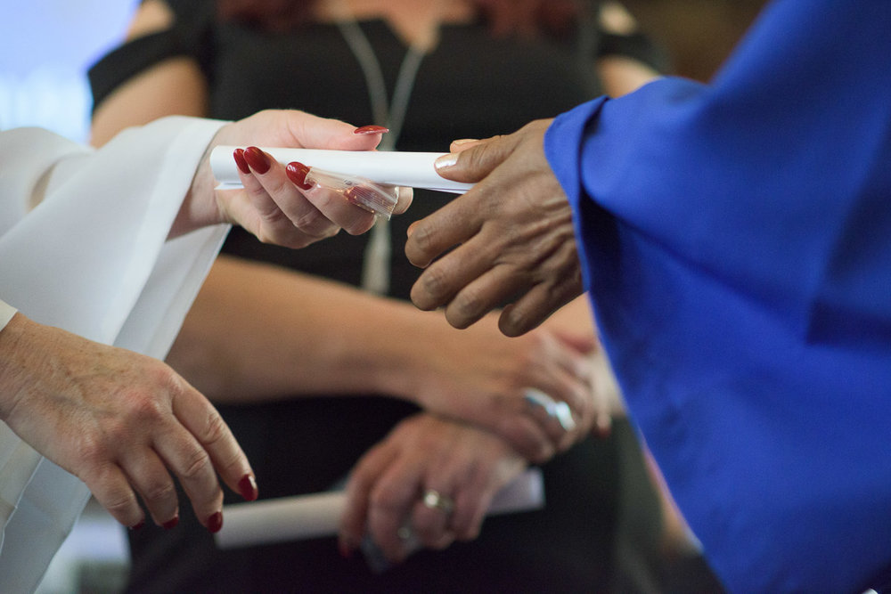An instructor hands a diploma to a graduate. This close-up shot focuses on their outstretched hands, highlighting the significance of this moment.