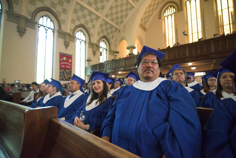 Rows of graduands seated on long benches listen to the commencement speeches. In this wide shot, the background is kept in focus in order to capture the grandeur of the ceremony hall.